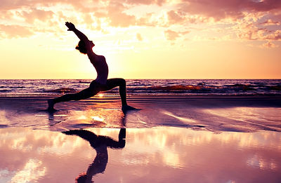 silhouette of woman practicing yoga on t