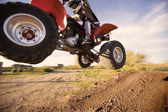 ATV 4 wheeler Motorsport vehicle jumping on dirt trail in Cheyenne, WY.