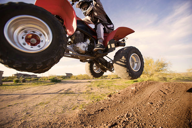 ATV 4 wheeler Motorsport vehicle jumping on dirt trail in Cheyenne, WY.