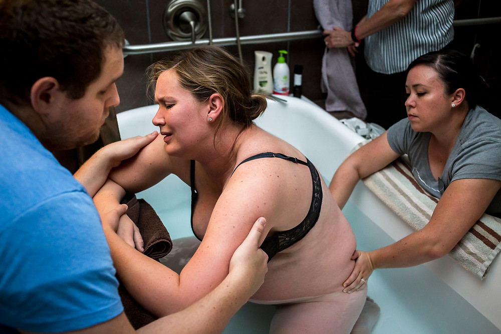 A doula gives counter pressure to a mom in labor during a contraction