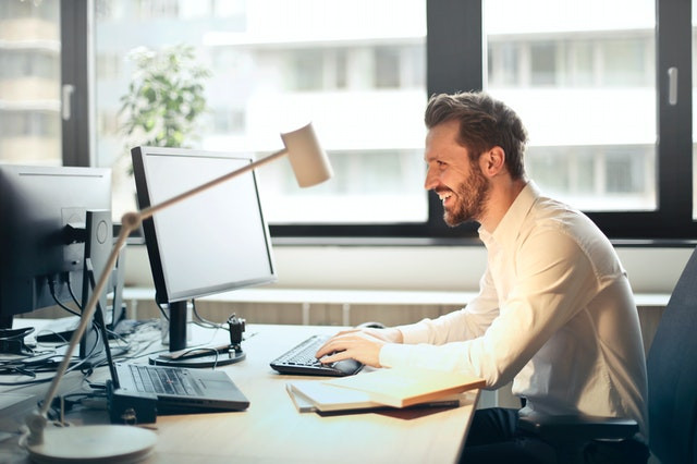 man sitting at desk with shoulders rounded forward