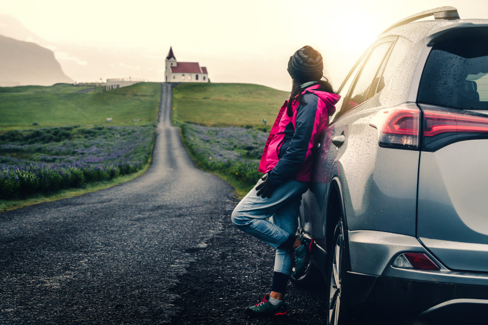 Girl with a rental car in Iceland looking at the views leaning on her car
