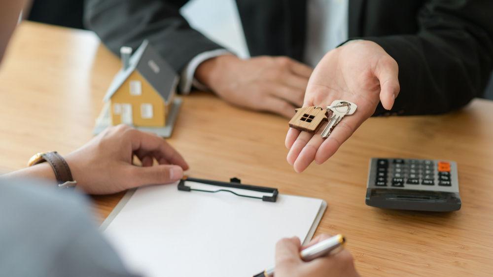 Agentes inmobiliarios de hipotecas en Islandia entregando las llaves al cliente