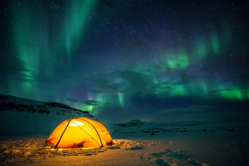 Tent set on snow and under the northern lights