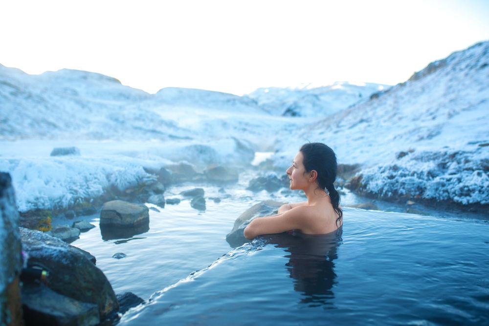 woman enjoying a warm bath in a hot spring in Iceland