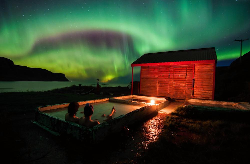 Pareja en un jacuzzi disfrutando de las auroras boreales en Islandia