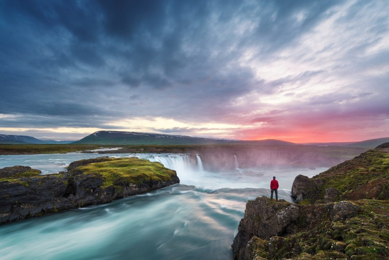 Visitor overlooking some waterfalls with the midnight sun in the background - Is Iceland worth visiting?