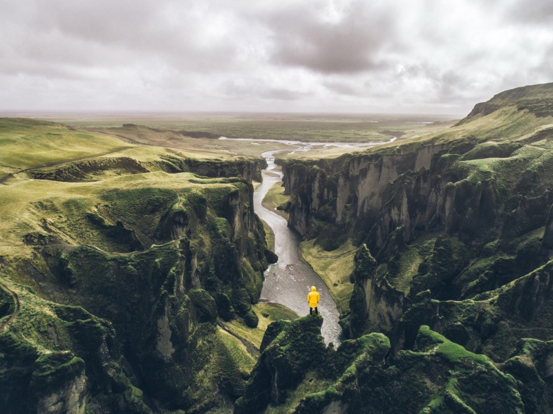 visitor overlooking a majestic gorge landscape in Iceland