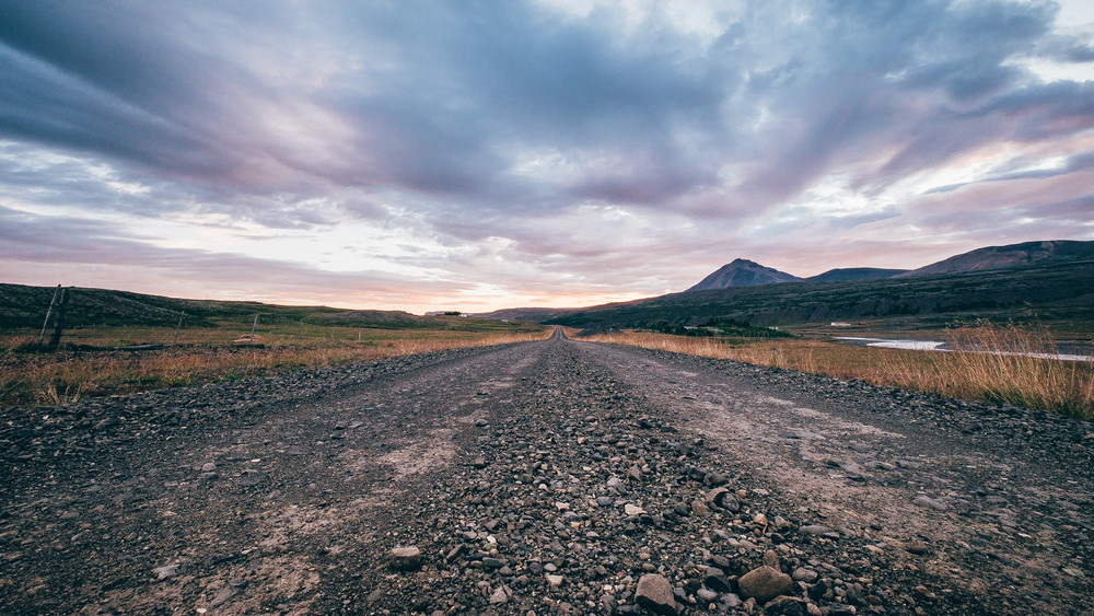 Image of a gravel road in Iceland with a beautiful pinkish sky