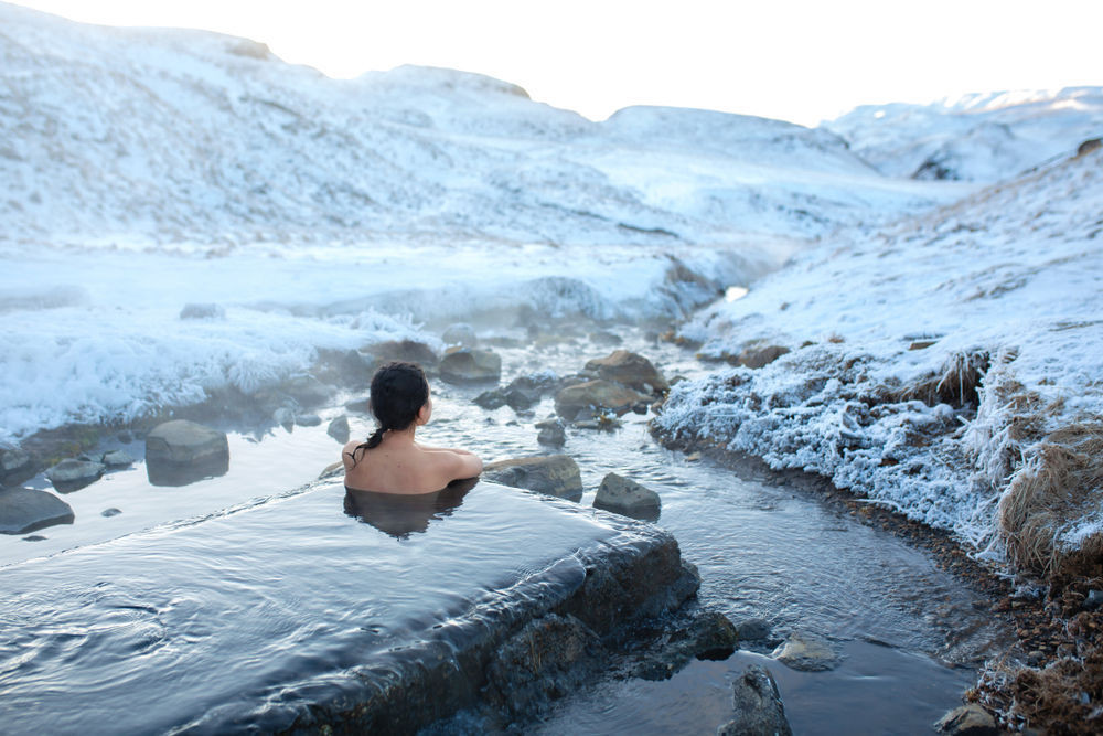Girl bathing in geothermal waters surrounded by a snowy mountains in winter