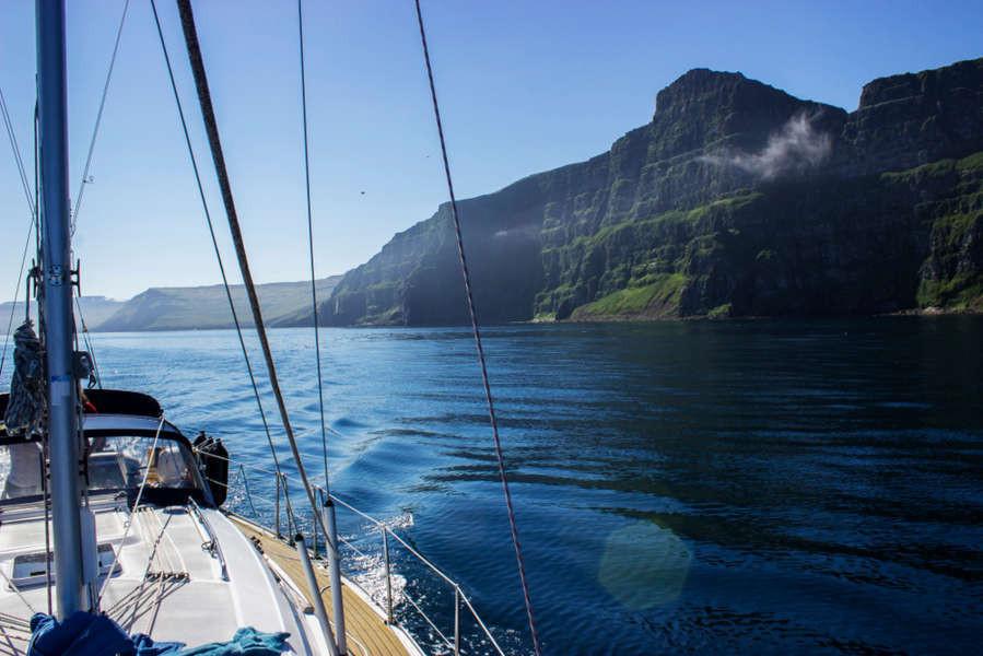 Boat sailing close to the Hornstrandir peninsula and cliffs