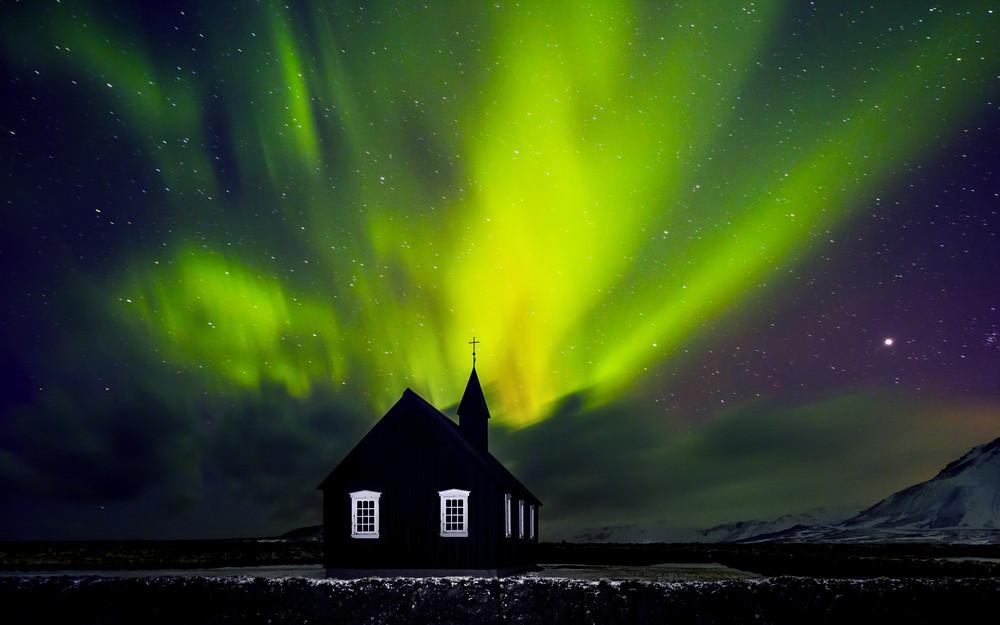 Iglesia negra bajo el cielo con auroras boreales en Islandia