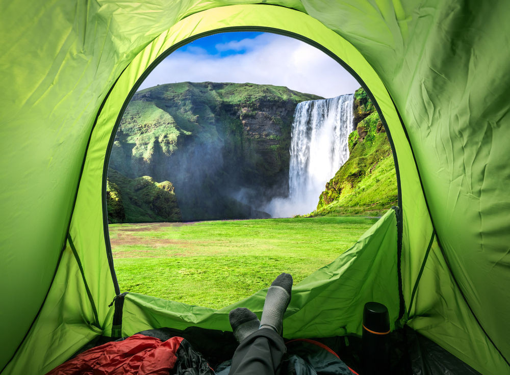 Camping in Iceland in front of a beautiful waterfall and the green meadows