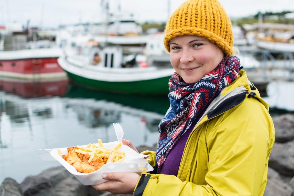 Chica comiendo comida callejera en Reikiavik junto al puerto