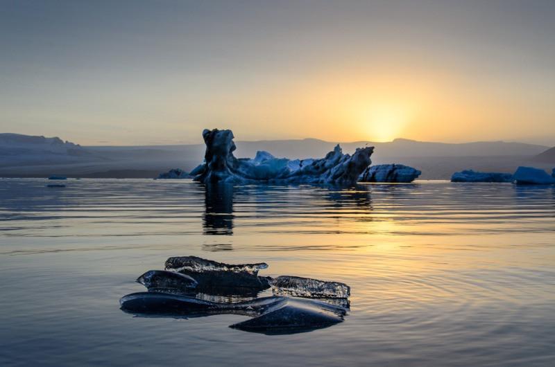 Sol de medianoche en Islandia en el horizonte detrás de una laguna glaciar