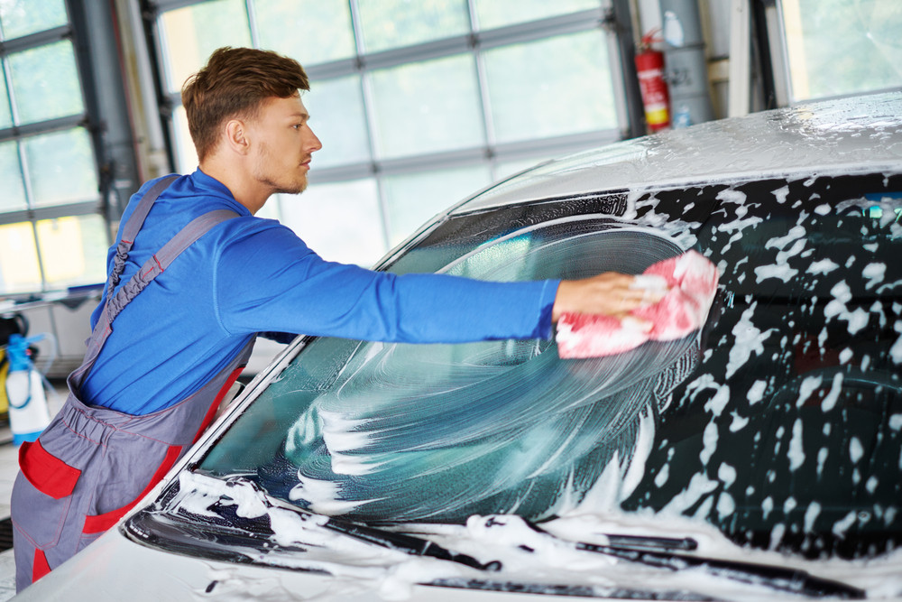 young man cleaning a car rental vehicle