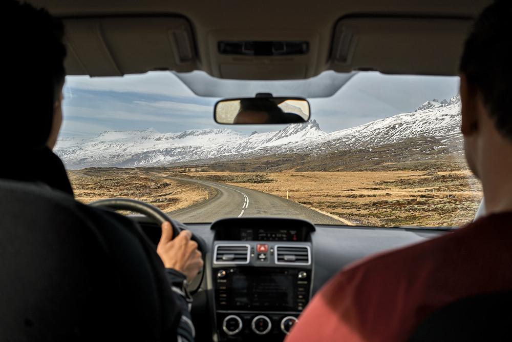 giovani uomini alla guida di un'auto a noleggio in Islanda