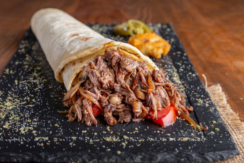 pulled lamb wrap served on a stone plate