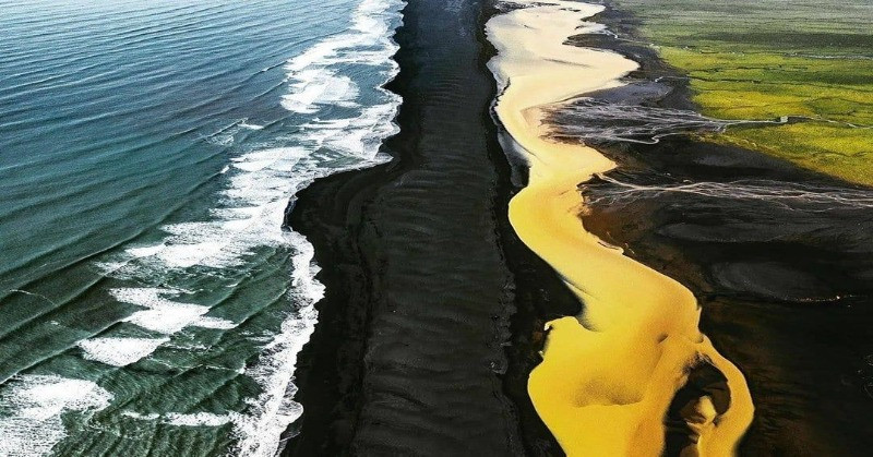 Unusual yellow river in Iceland in contrast with the black sand beach and a green moss field