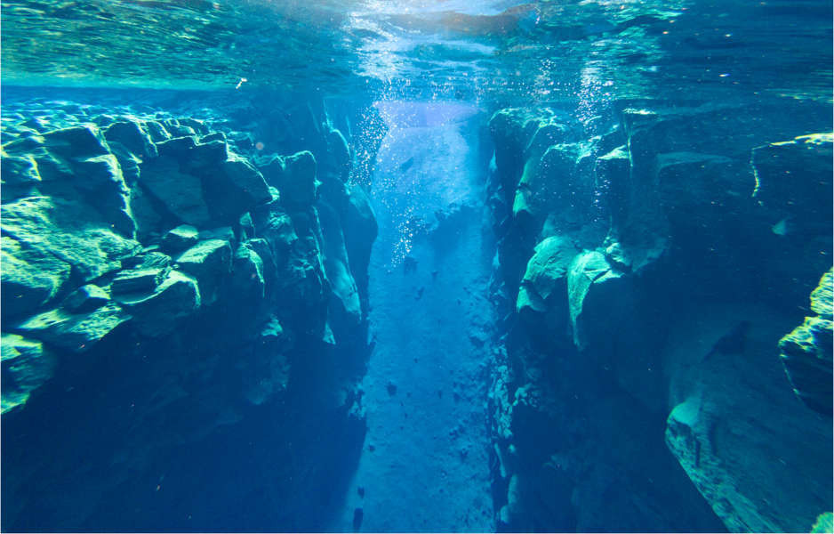diver swimming in the Silfra fissure, visible thanks to earthquakes in Iceland