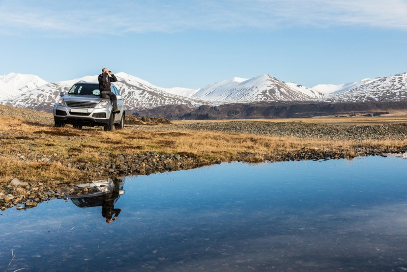Men seating on his rental car in icelandic landscape