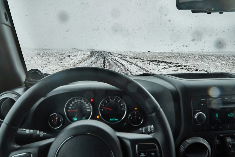 Rental car driving in winter in Iceland on a snowy gravel road