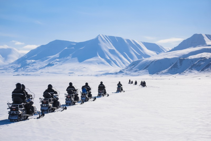 a group of tourist snowmobiling in Iceland in a landscape full of snow