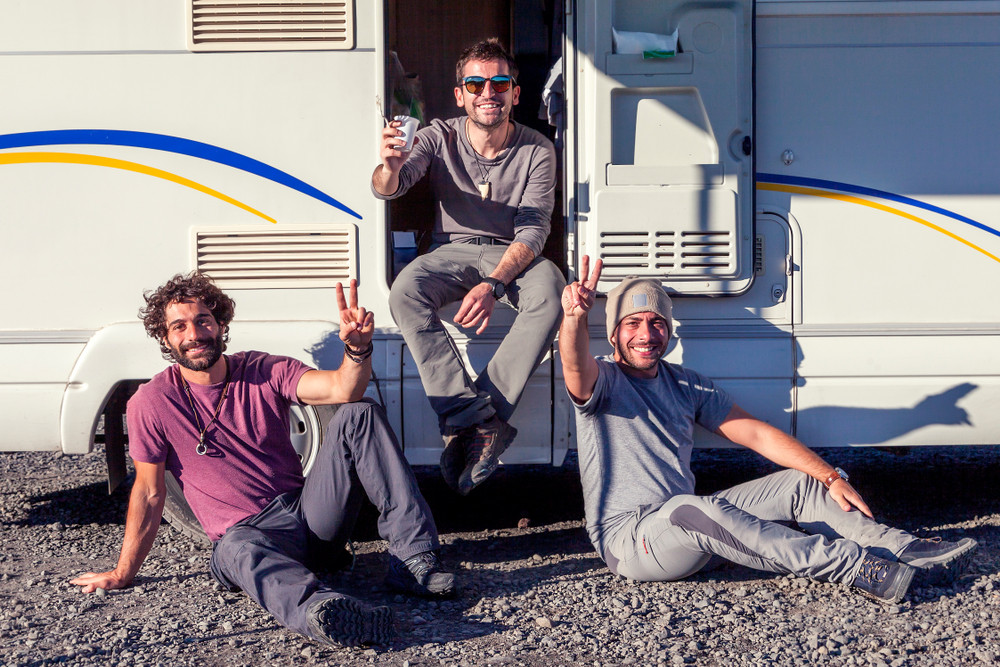 Three young man enjoy the sun by their motorhome - camper van's heating system iceland