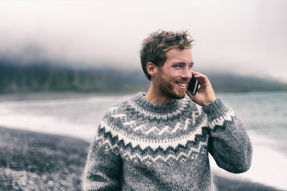 young man using a sim card for Iceland travels making a call by the ocean