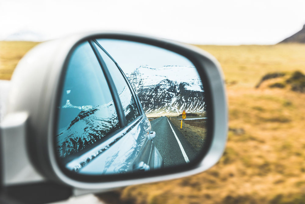Picture of a mountain ridge reflecting on a car's rear view mirror