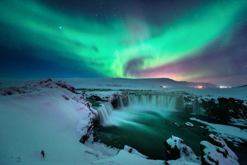 Iceland's Northern Lights over Godafoss waterfall on a snowy winter night