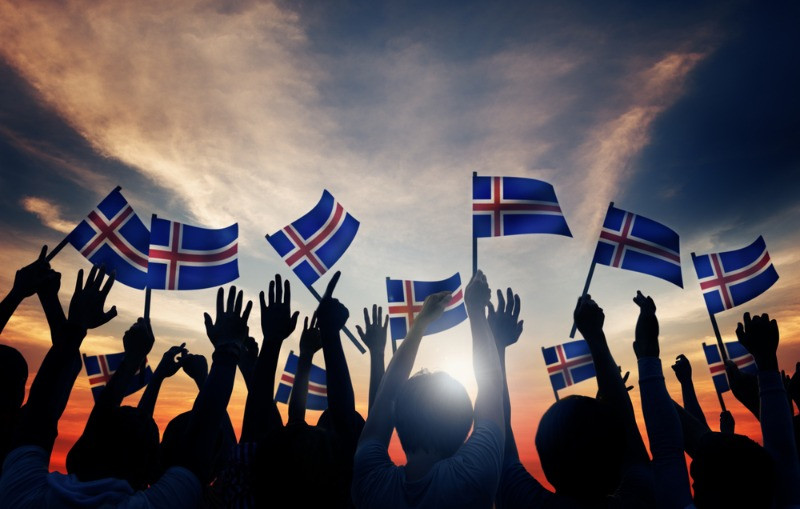 Crowd holding flags of Iceland - Iceland demographics