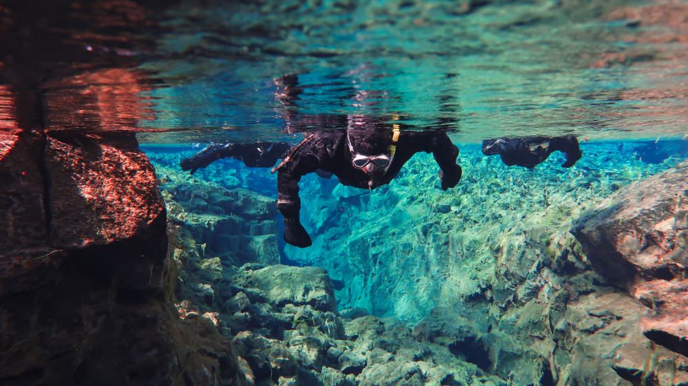 tourist diving in silfra, where the tectonic plates meet in the map of Iceland