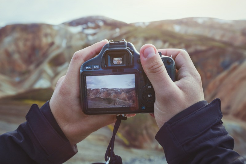 young man taking pictures of the icelandic landscape with a reflex camera