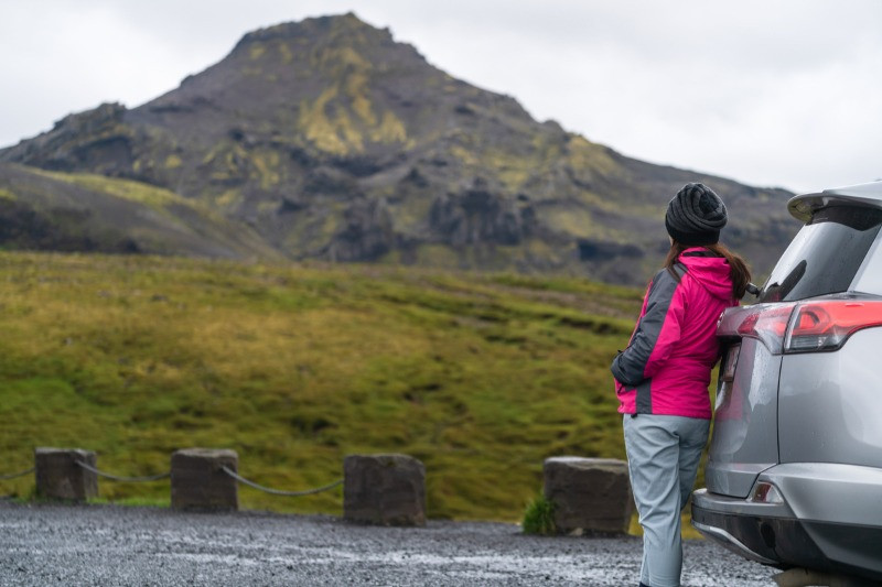 Woman in Icelandic landscape with best road trip cars