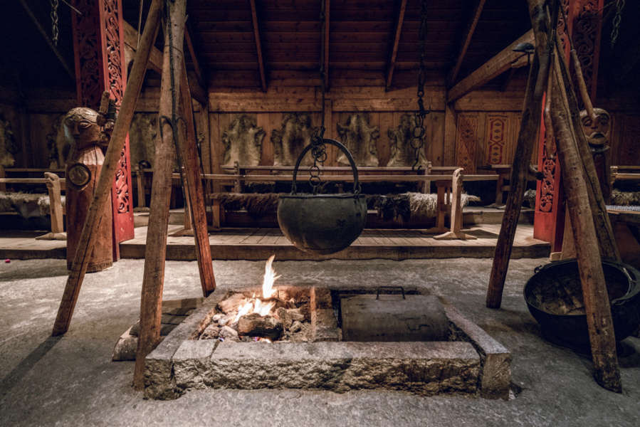 interior of a viking house with a bonfire in the central area