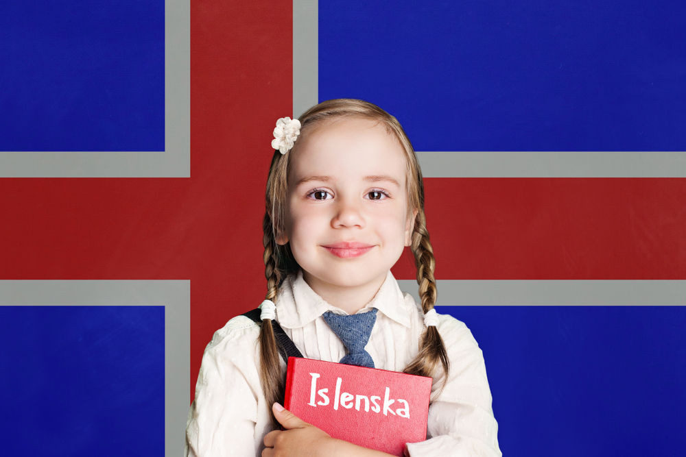 Little girl holding her Icelandic workbook with the Icelandic flag behind her