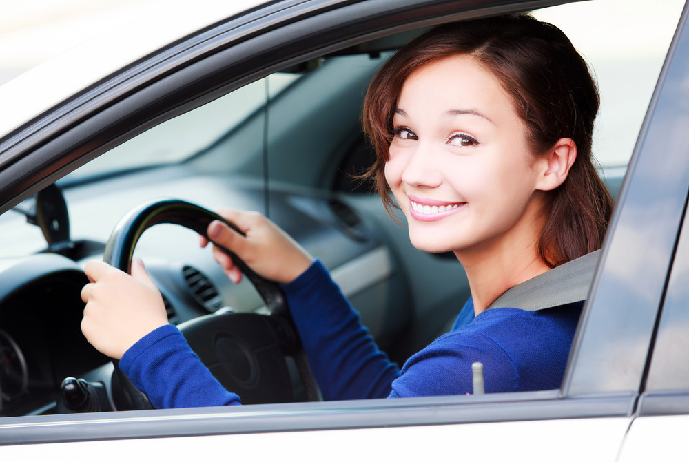 Young woman driving her rental car as she meets the minimum driving age in Iceland