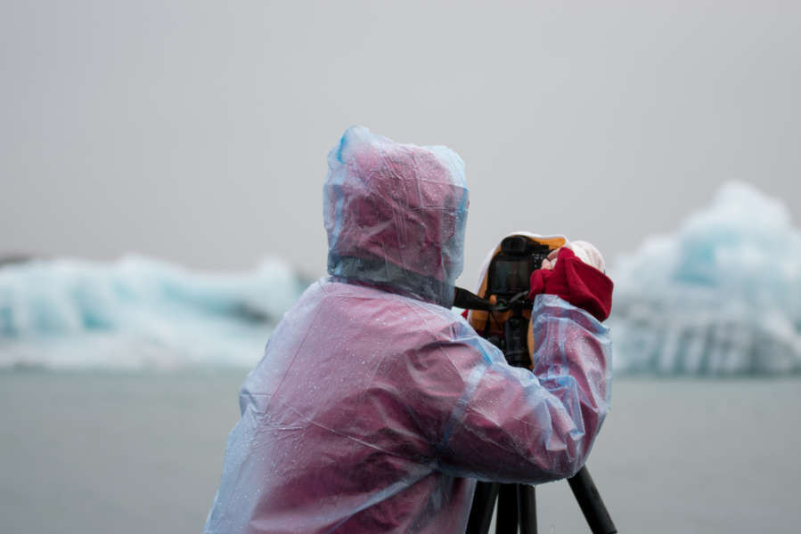 photographer wearing a raincoat and protecting his equipment in a photo tour