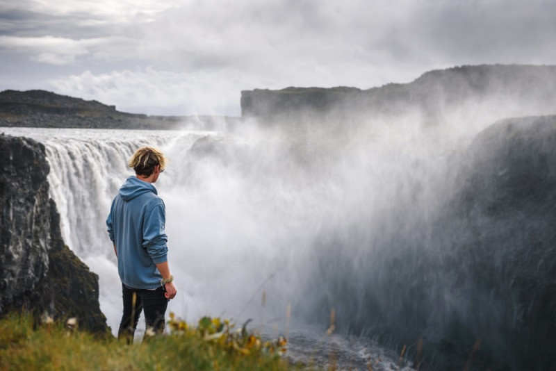 Young man overlooking the Dettifoss waterfall in Iceland's diamond circle