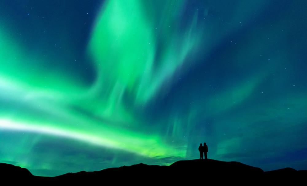 novelli sposi che si godono l'aurora boreale
