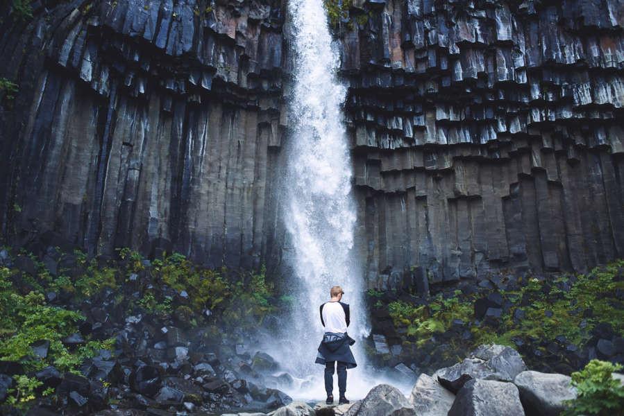 giovane uomo in posa davanti alla cascata svartifoss nel sud dell'Islanda