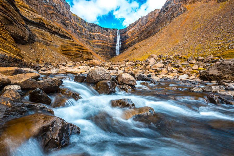 Beautiful shot of the Hengifoss waterfall from far away in a yellowish landscape