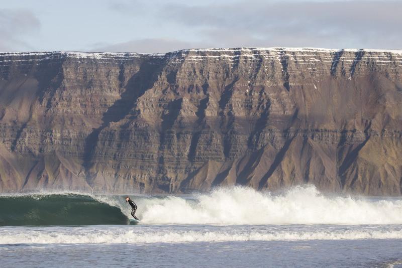 Chico surfeando delante de una imponente montaña islandesa