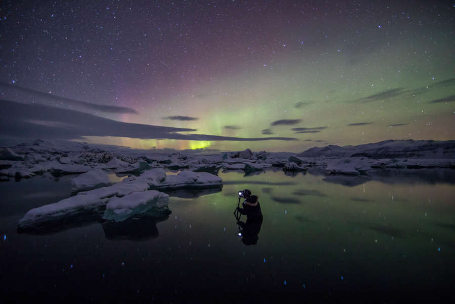 photo tour in Iceland, photographer taking a picture of the aurora borealis