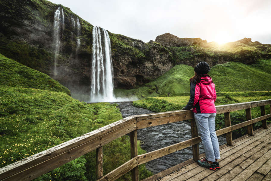 Girl looking at Seljalandsfoss waterfall from the fence