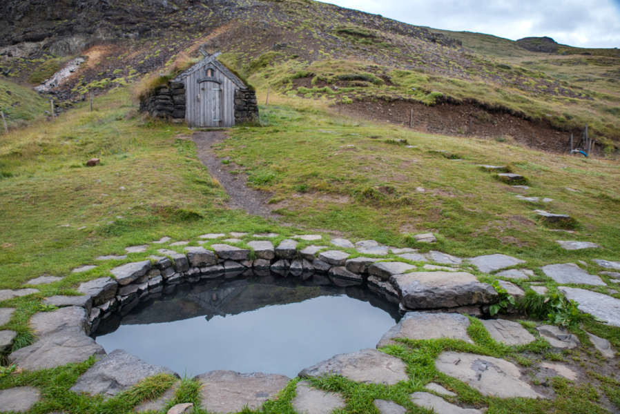 hot spring close to a typical Icelandic turf house
