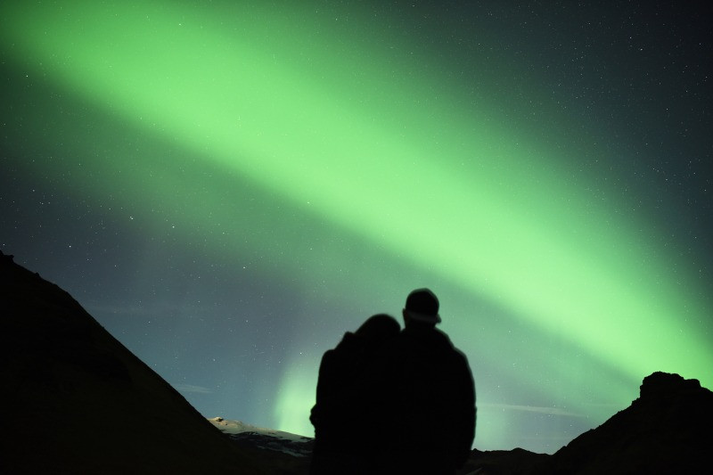 Iceland honeymoon couple watching the Northern Lights