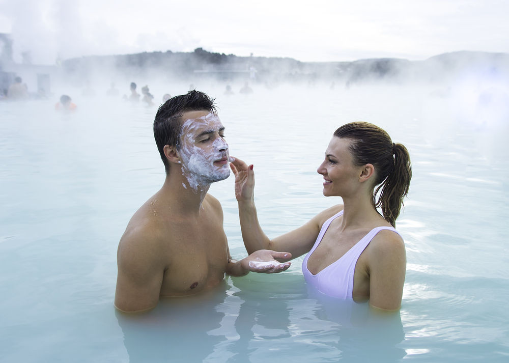 woman rubbing silica and creating a face mask on a man's face