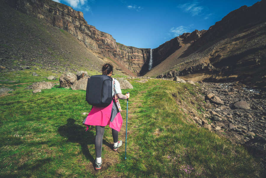 Woman hiking to Hengifoss waterfall, which can be seen on the horizon